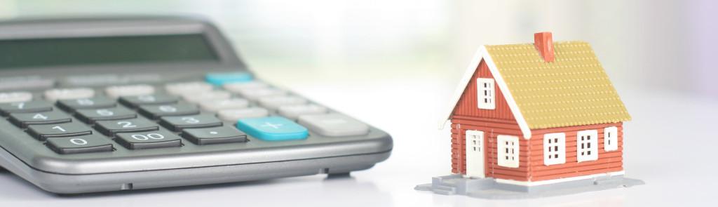 Calculatrice posée à côté d'une maison miniature